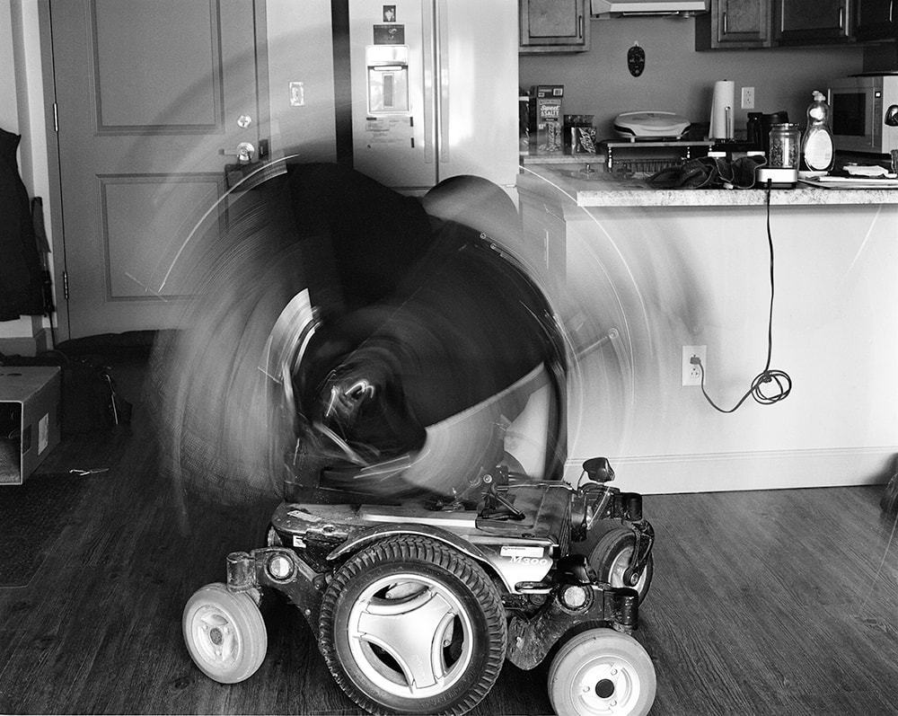 A black and white photo of a power wheelchair. The seat is blurred with the motion of rocking back and forth.