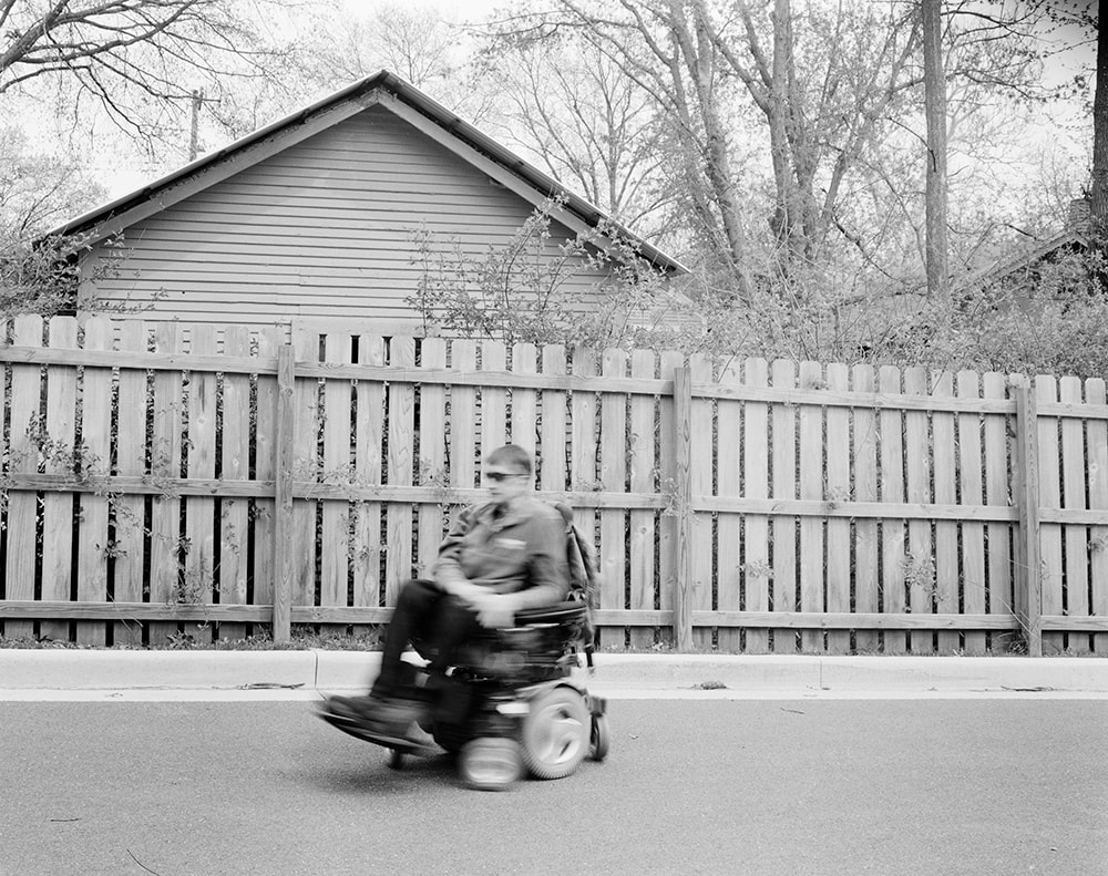 A black and white photo of a man in a power wheelchair riding in front of a wood fence. The man and his chair are blurred with forward motion.