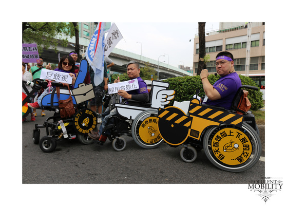 Three wheelchair riders pose with signs in Taiwanese. The chairs are decorated tas an office chair with a briefcase, an accessible toilet, and an accessible vehicle..