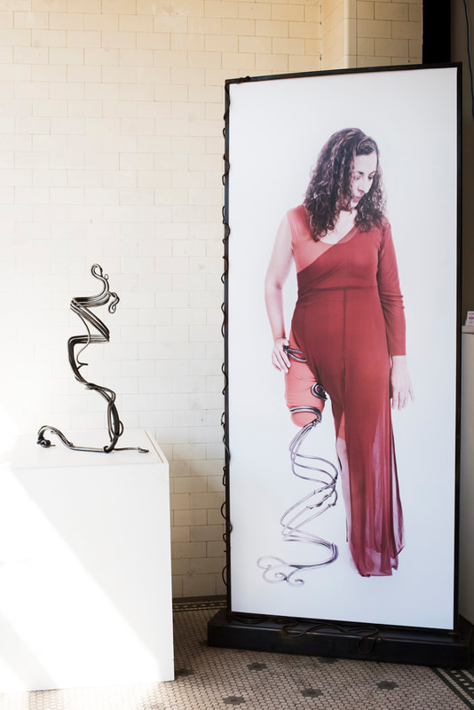 On the left is a swirled metal prosthetic leg and on the right a large photo of a white woman in a red dress wearing that leg.