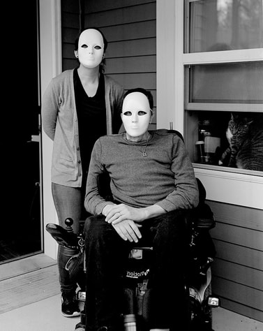 A black and white photo of two people in white masks. One stands at the left, the other sits in a wheelchair on the right.