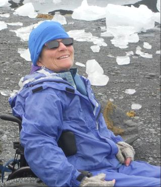 Photo of a smiling white woman wearing a blue cap and coat and a pair of sunglasses. She is in a wheelchair in front of an icy field.