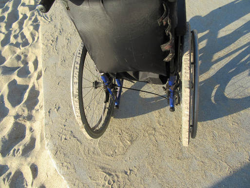 A pair of wheelchair wheels carved so that they leave imprints of words in the sand.