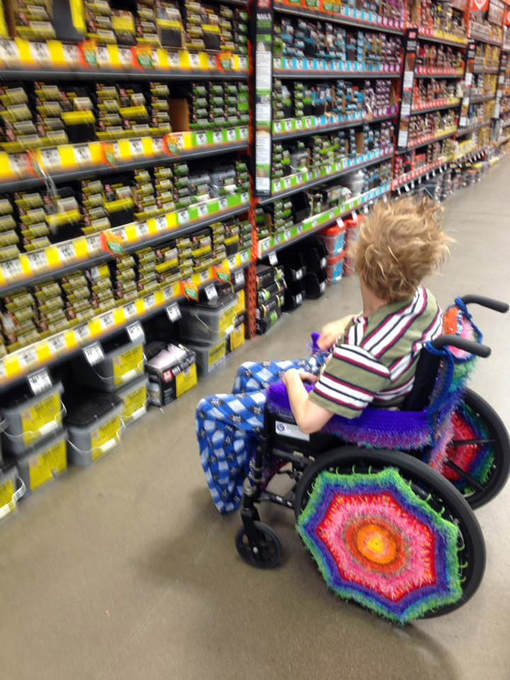 The bright yarn-bombed wheelchair with a blonde, tousled hair rider in front of a row of hardware shelves.