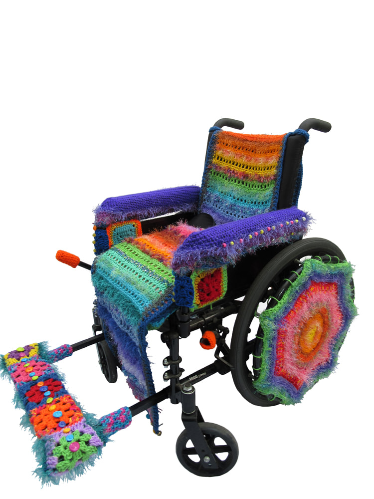 A wheelchair covered in brightly colored crocheted yarns..